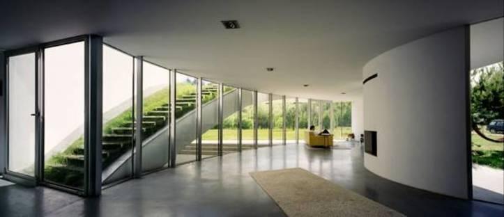 Wohnzimmer mit verglaster Wand und Zugang zum Dachgarten