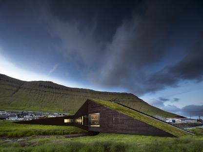Ein brückenförmiges Rathausaus Beton und Holz über den Fluss von Henning Larsen
